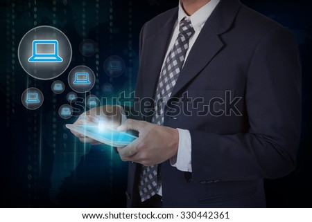 Businessman hand touch laptop icons on a tablet.
