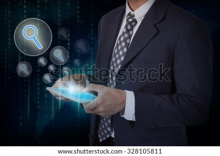 Businessman hand touch search icons on a tablet - stock photo