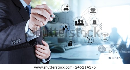 businessman hand touch Wind turbines with his office background - stock photo