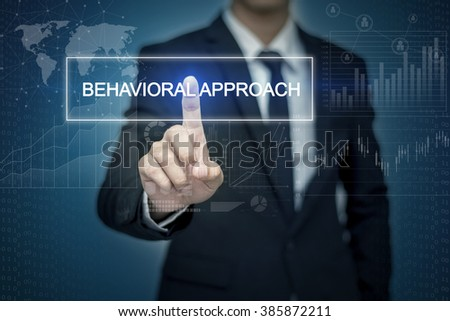 Businessman hand touching BEHAVIORAL APPROACH  button on virtual screen