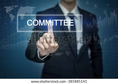 Businessman hand touching COMMITTEE  button on virtual screen