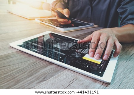 Businessman hand touching digital tablet.Photo finance manager working new Investment project office.Using new technology device.Graphic icons.Strategy business stock exchanges interface layer effect  - stock photo