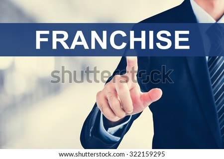 Businessman hand touching FRANCHISE word on virtual screen - stock photo