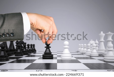 Businessman hand touching king pawn on chess board. Gray background. Business concept - stock photo