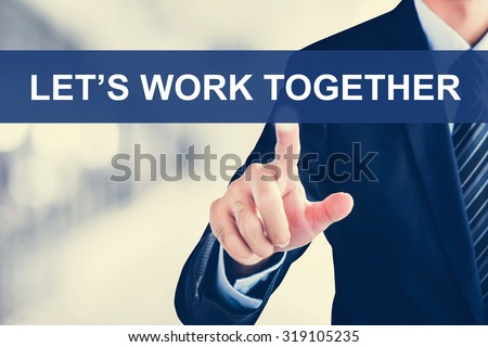 Businessman hand touching LET'S WORK TOGETHER message on virtual screen - stock photo