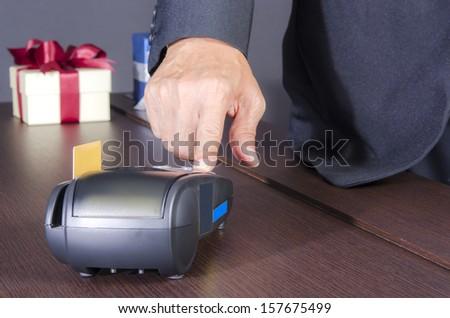 Businessman hand using credit machine - stock photo