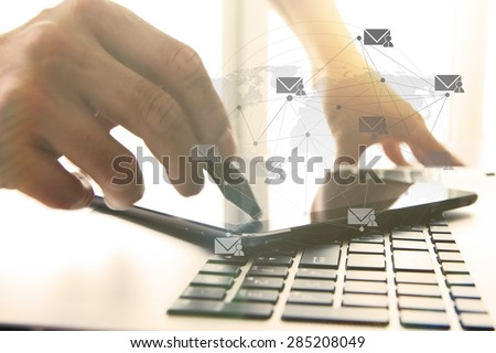 Businessman hand using laptop and digital tablet in office with social media diagram - stock photo