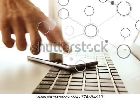 Businessman hand using laptop and mobile phone in office - stock photo