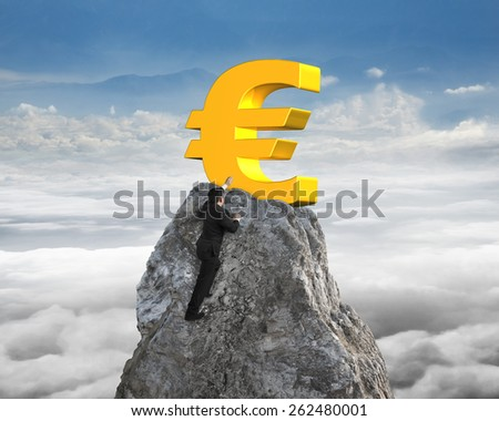 Businessman hand wanting for gold euro symbol on mountain peak with sky cloudscape background - stock photo
