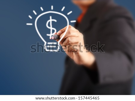 businessman hand with a pen drawing light bulb inside is dollars - stock photo
