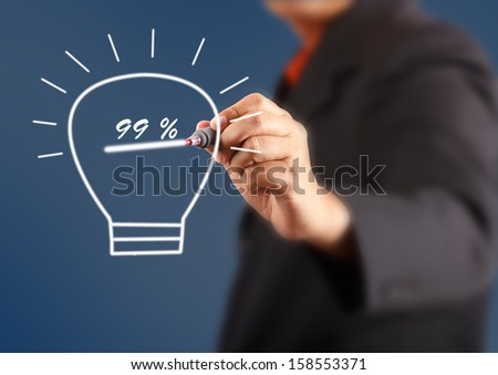 businessman hand with a pen drawing light bulb inside is percent - stock photo