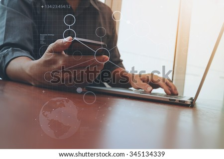 businessman hand working and smart phone and laptop with social media diagram on wooden desk in office - stock photo