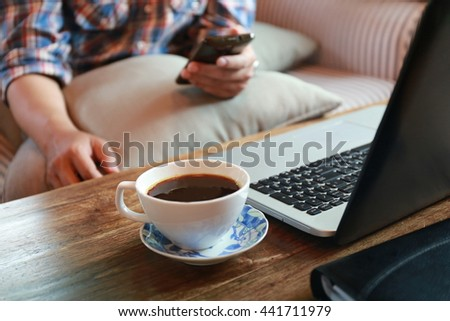 businessman hand working on phone and laptop, Hands multitasking working on laptop connecting internet at office desk, man relaxing with phone on sofa at living room.  - stock photo