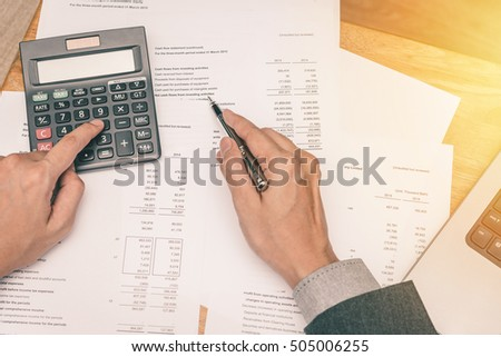 Businessman hand working with balance sheet paper. Photo with sunlight filter effect.