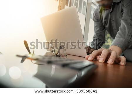 businessman hand working with new modern computer and smart phone and business strategy on wooden desk with calculator and eyeglass foreground as concept - stock photo