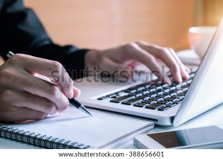businessman hand working with new modern computer and writing on the notepad strategy diagram as concept morning light