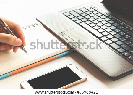 businessman hand working with new modern computer and writing on the notepad strategy diagram as concept morning light, soft focus