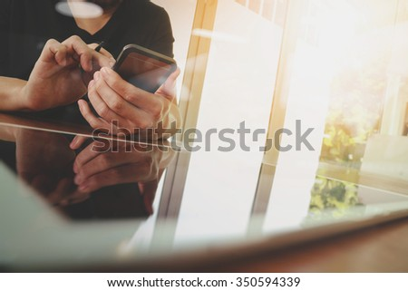 businessman hand working with new tablet modern computer and smart phone on wooden desk - stock photo