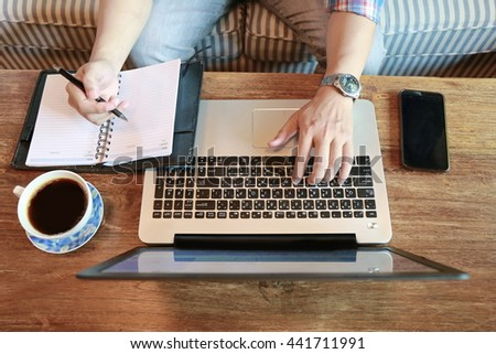 businessman hand write pen on notebook and work on laptop, hand multitasking working on laptop connecting internet at office desk, man relaxing on sofa at living room.  - stock photo