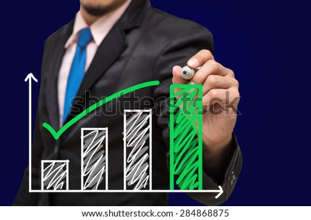 Businessman hand writing a graph on dark blue background, Business investment concept - stock photo