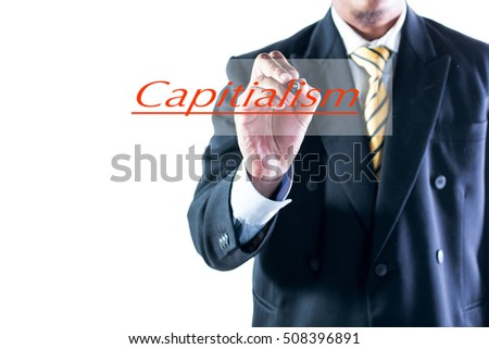 Businessman hand writing Capitialism on transparent wipe board.