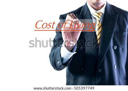 Businessman hand writing Cost of living on transparent wipe board.