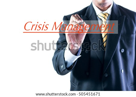Businessman hand writing Crisis Management  on transparent wipe board.