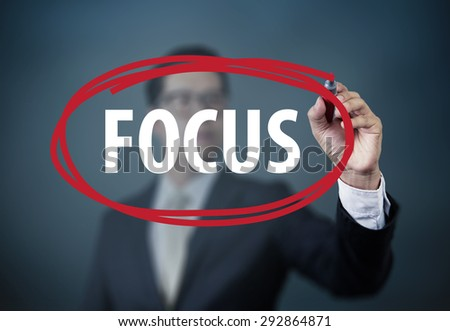 "Businessman hand writing ""FOCUS"" with red marker on transparent board, new business concept, studio shot - stock photo"