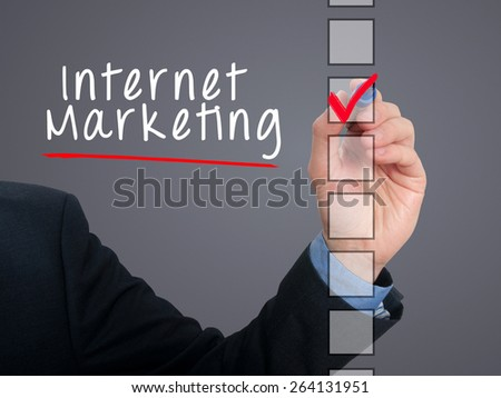 Businessman hand writing Internet Marketing and check listing task. Isolated on grey background. Stock photo
