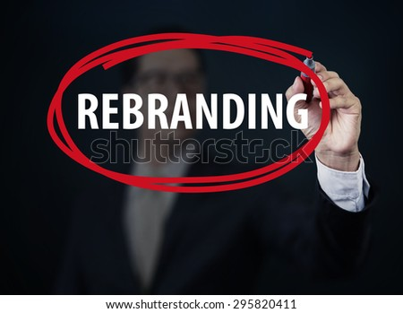 "Businessman hand writing ""REBRANDING"" with red marker on transparent board, new business concept, studio shot - stock photo"
