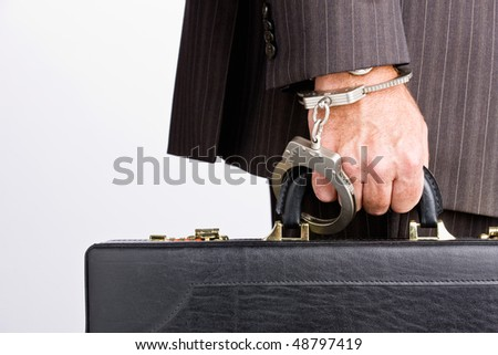 Businessman handcuffed to briefcase - stock photo