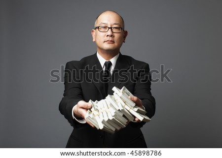 Businessman handing out bundles of cash.
