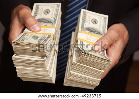 Businessman Handing Over Stacks of Hundred Dollar Bills. - stock photo