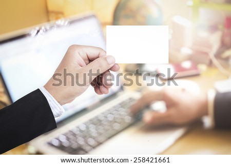 Businessman hands holding a blank business card over blurred working people in office background. - stock photo