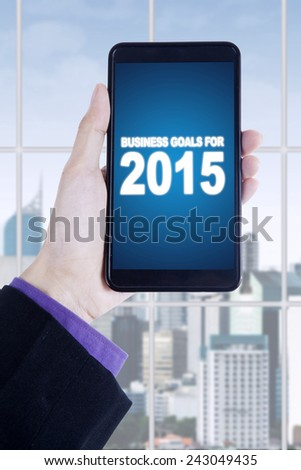Businessman hands holding a smartphone with a text of business goals for 2015