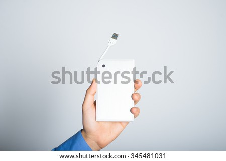 businessman hands holding an external usb hard drive. advertising concept, isolated on a gray background. - stock photo