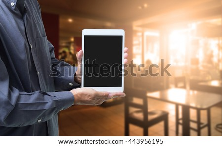 Businessman hands holding blank screen tablet phone with blur coffee shop background - stock photo