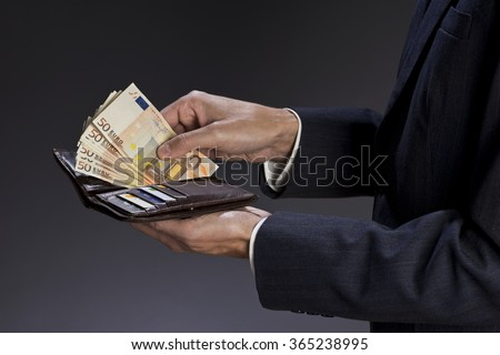 Businessman hands holding wallet with credit cards and stack of money, euro bills. Fifty euros banknotes, isolated gray background. - stock photo