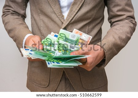 Businessman hands holding wallet with stack of euro bills money