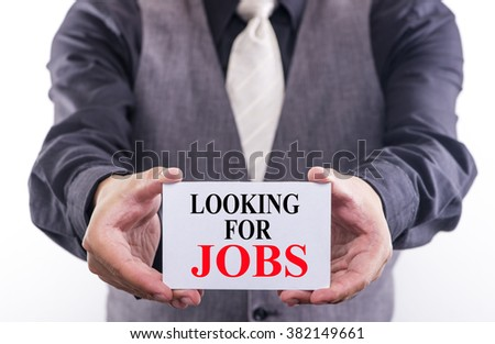 Businessman hands holding white card with Looking For Jobs sign written