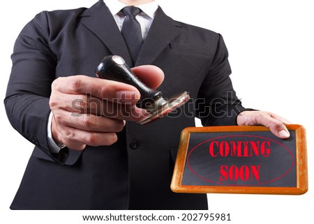 businessman hands put the stamp wood blackboard red coming soon word stamp on white background with clipping path - stock photo