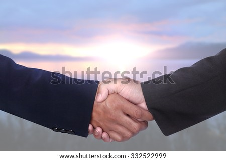 businessman hands shaking together for agreement success over blur blurred morning light at the nature point of snow mountain and calm lake Abisko Sweden - stock photo