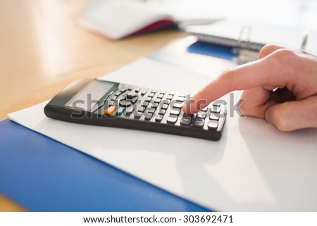 Businessman hands typing on calculator in his office
