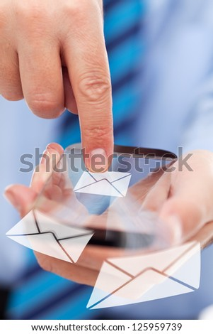Businessman hands with futuristic transparent smartphone sending mail messages - stock photo