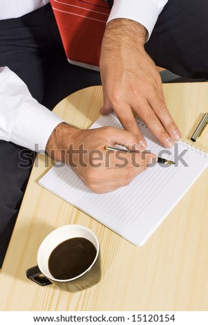 Businessman hands with notepad and coffee - coffeebreak concept