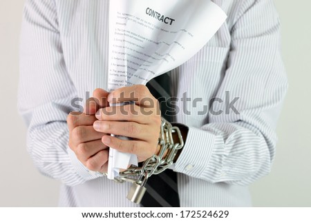 Businessman hands with tied with chains and hold contract - stock photo