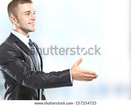 businessman handshake, hold hand welcome gesture, Handsome young excited business man happy smile wear elegant suit and tie - stock photo