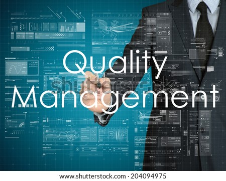 businessman handwriting Quality Management on a transparent board - stock photo