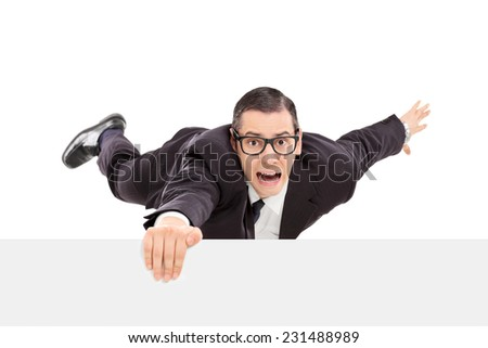 Businessman hanging on the edge of a white panel isolated on white background - stock photo