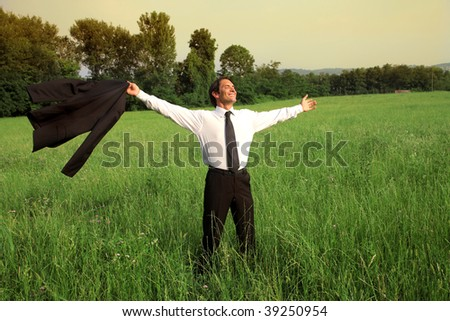 businessman happy and carefree standing  in a grass field - stock photo